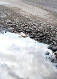Wassergefülltes Schlagloch in der Straße Lizenzfreies Stockbild