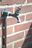 Wasserhahn befestigt zu einer Backsteinmauer Lizenzfreie Stockfotografie