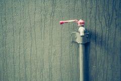 Wasserhahn im Freien auf Backsteinmauer mit Regen fällt Stockbild