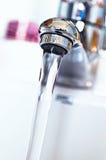 Wasserhahn mit flüssigem Wasser im Badezimmer Stockfotografie