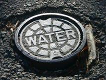 Wasserhauptleitungs-Einsteigelochabdeckung Stockfotografie