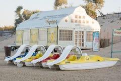 Wasserkatamaran sind auf dem Sand vor einem Café auf dem Strand am frühen Morgen Lizenzfreie Stockfotos
