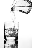 Wasserkrug, der in Glas gießt Stockbilder
