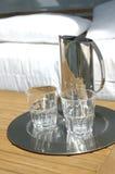 Wasserkrug und -gläser durch Bett Stockfotos
