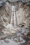Wasserleitungen im Boden während des KlempnerarbeitBaustelle-Grubengrabens geben mit einem Graben um Lizenzfreies Stockbild