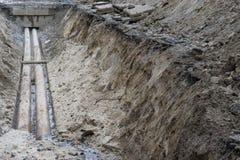 Wasserleitungen im Boden während des KlempnerarbeitBaustelle-Grubengrabens geben mit einem Graben um Lizenzfreie Stockfotos