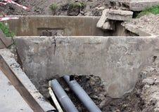 Wasserleitungen, Isolierüberdachung bedeckt während der Reparatur in einem Abzugsgraben, der mit schlammiger Flüssigkeit gefüllt  Stockfotografie