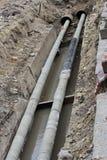 Wasserleitungen, Isolierüberdachung bedeckt während der Reparatur in einem Abzugsgraben, der mit schlammiger Flüssigkeit gefüllt  Lizenzfreie Stockfotografie