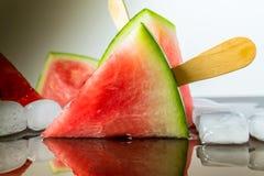 Wassermelone schnitt Scheibe auf einem Stock von der Eiscreme in der Eiswürfelnahaufnahme mit Reflexion Stockbild