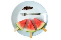Wassermelone schnitt Scheibe auf einem Stock von der Eiscremenahaufnahme auf weißer Platte mit der lokalisierten Gabel Lizenzfreie Stockbilder