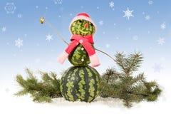 Wassermelonen-Schneemann im roten Hut und im Schal mit Tannenzweig auf blauem Hintergrund und fallenden Schneeflocken Lizenzfreies Stockfoto