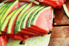 Wassermelonenfrucht geschnitten in Stücke auf dem Bretterboden. Lizenzfreies Stockbild