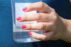 WassermelonenNagellack und ein Glas des Wasserfeiertags Stockfotografie