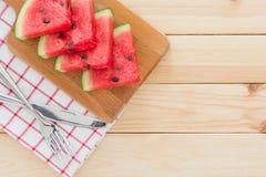 Wassermelonenscheiben auf einem hölzernen Brett, gedient mit Tischbesteck und Serviette auf einem Holztisch Lizenzfreie Stockbilder