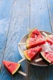 Wassermelonenscheibeneis am stiel auf einem blauen rustikalen hölzernen Hintergrund stockbild
