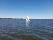 Wassernote der Himmel und ein Segelboot Lizenzfreie Stockfotos
