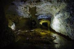 Wasserreflexionen innerhalb des dunklen schmutzigen überschwemmten verlassenen Bergwerkes stockfotos