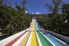 Wasserrutsche mit hellen farbigen Bahnen in der Aquaparkeinfassung Lizenzfreie Stockfotos
