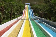 Wasserrutsche mit hellen farbigen Bahnen in der Aquaparkeinfassung Stockfotos