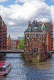Wasserschloss with boat in Hamburg Speicherstadt, Germany. Sight seeing boat in Wasserschloss in Hamburg Speicherstadt, Germany with blue skies on sunny day Stock Images