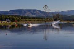 Wasserski-männlicher Slalom, der Spray-Landschaft schnitzt Lizenzfreie Stockfotografie
