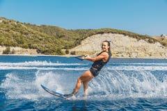 Wasserskis gleitet auf den Wellen, weiblicher Athlet auf Ägäischem Meer, Griechenland Lizenzfreies Stockfoto