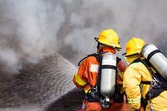 Wasserspray mit zwei Feuerwehrmännern durch die Hochdruckdüse, zum von sur abzufeuern Stockfotografie