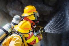 Wasserspray mit zwei Feuerwehrmännern durch die Hochdruckdüse, zum von sur abzufeuern Stockfoto