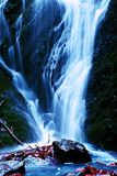 Wasserspray unter kleinem Wasserfall auf Gebirgsstrom, Wasser fällt über moosigen Flussstein Der Spray schaffen auf Niveau und Ki Lizenzfreie Stockbilder