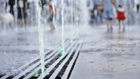 Wassersprays eines Bodenbrunnenabschlusses up und eine Frau mit einem Kind, das das Leben weg genießen laufen lässt stock video