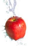 Wasserspritzen auf einem frischen roten Apfel Lizenzfreie Stockfotos