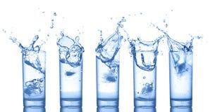 Wasserspritzen in den Gläsern auf Weiß Stockfoto
