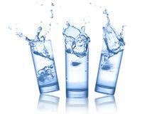 Wasserspritzen in den Gläsern auf Weiß Stockbild