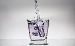 Wasserspritzen in einem Glas Stockbild