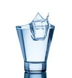 Wasserspritzen im Glas getrennt auf Weiß Lizenzfreies Stockbild