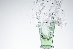 Wasserspritzen im grünen trinkenden Glas Stockbilder