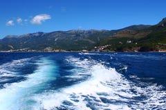Wasserspuren hinter schnellem Boot mit Landschaft Lizenzfreies Stockfoto