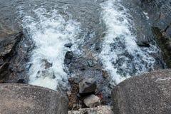 Wasserströme vom Abflussrohr in den Fluss Lizenzfreie Stockfotografie