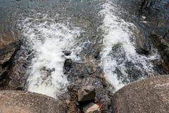 Wasserströme vom Abflussrohr in den Fluss Stockfotografie