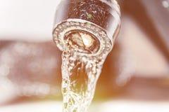 Wasserströme vom Hahn, greller Glanz von der Sonne, Verstopfung von Wasserleitungen, inländisches Abwasser Stockfoto