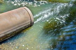 Wasserströme vom Rohr in den Fluss Stockfotos
