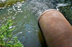 Wasserströme vom Rohr in den Fluss Stockbild