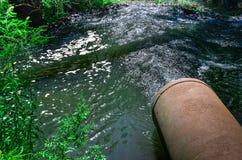 Wasserströme vom Rohr in den Fluss Stockfoto