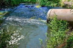 Wasserströme vom Rohr in den Fluss Stockbilder