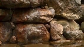 Wasserstrahlen, die über Felsen in einen Teich fließen stock video