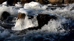 Wasserströme über den gefrorenen Felsen stock footage