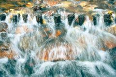 Wasserstromüberlauf durch hölzernes Wehr im Fluss Stockfotografie