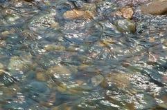 Wasserstrom über mehrfarbigen Steinen Stockbild