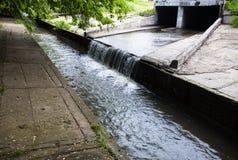 Wasserstrom, der heraus der Untertagetunnel fließt Stockbilder