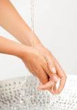 Wasserstrom und Spritzen auf Händen der Frau Stockbild
